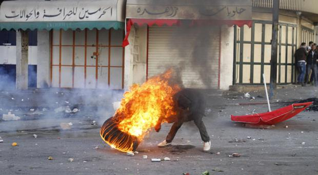 A Palestinian pushes a burning tire during clashes with Israeli troops against Israel's operations in Gaza Strip in the West Bank city of Hebron. Tuesday, Nov. 20, 2012.(AP Photo/Nasser Shiyoukhi)