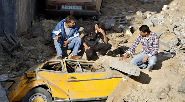 Palestinians sit on the debris left after an overnight Israeli strike in Bureij refugee camp, Gaza Strip, Tuesday, Nov. 20, 2012