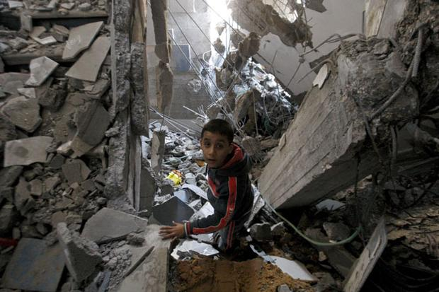 A Palestinian boy stands in the rubble left after an Israeli strike on a house in Gaza City, Tuesday, Nov. 20, 2012
