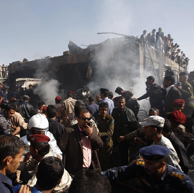 Army and police officers work at the scene of a plane crash in Sanaa, Yemen (AP)