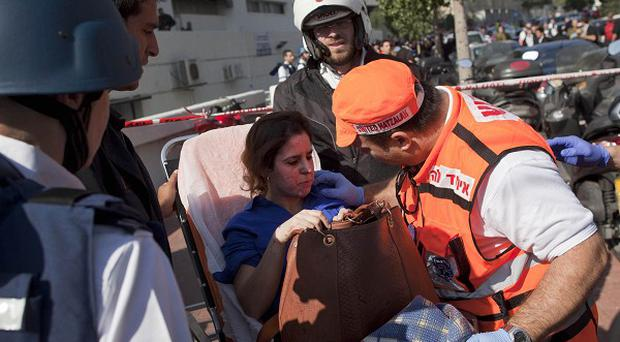Rescue workers carry an injured woman from the bus bombing in Tel Aviv( AP)