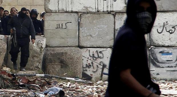 A protester confronts riot police in Cairo (AP)