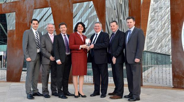John Rainey, chairman of Denroy Plastics, and colleagues receive their bronze category award from Enterprise Minister Arlene Foster and Stephen Cowan from Bombardier at the SC21 awards