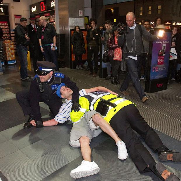 Lee Nelson is restrained by an actor playing a policeman and a real community support officer