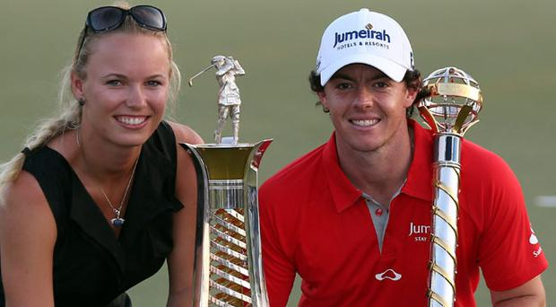 DUBAI, UNITED ARAB EMIRATES - NOVEMBER 25: Caroline Wozniacki of Denmark and Rory McIlroy of Northern Ireland with the DP World Tour Championship and The Race to Dubai trophy on the 18th green during the final roung of the DP World Tour Championship on the Earth Course at Jumeirah Golf Estates on November 25, 2012 in Dubai, United Arab Emirates. (Photo by Ross Kinnaird/Getty Images)