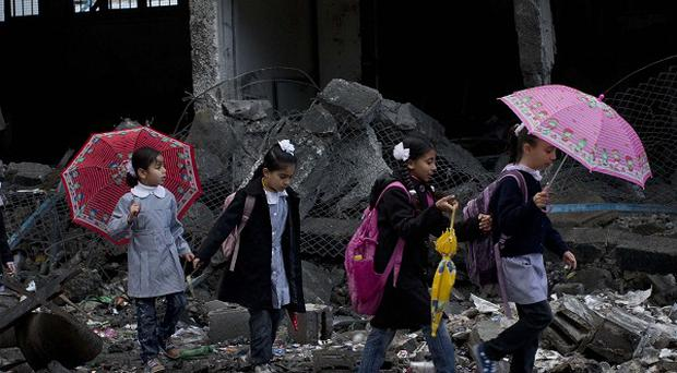 Palestinian schoolchildren walk in debris in Gaza City. Schools in Gaza have reopened for the first time since the truce was agreed. (AP)