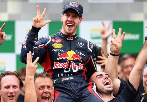 SAO PAULO, BRAZIL - NOVEMBER 25: Sebastian Vettel of Germany and Red Bull Racing celebrates with team mates on the podium as he finishes in sixth position and clinches his third consecutive drivers world championship during the Brazilian Formula One Grand Prix at the Autodromo Jose Carlos Pace on November 25, 2012 in Sao Paulo, Brazil. (Photo by Paul Gilham/Getty Images) *** BESTPIX ***