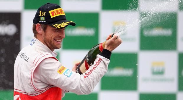 SAO PAULO, BRAZIL - NOVEMBER 25: Jenson Button of Great Britain and McLaren celebrates on the podium after winning the Brazilian Formula One Grand Prix at the Autodromo Jose Carlos Pace on November 25, 2012 in Sao Paulo, Brazil. (Photo by Clive Mason/Getty Images)