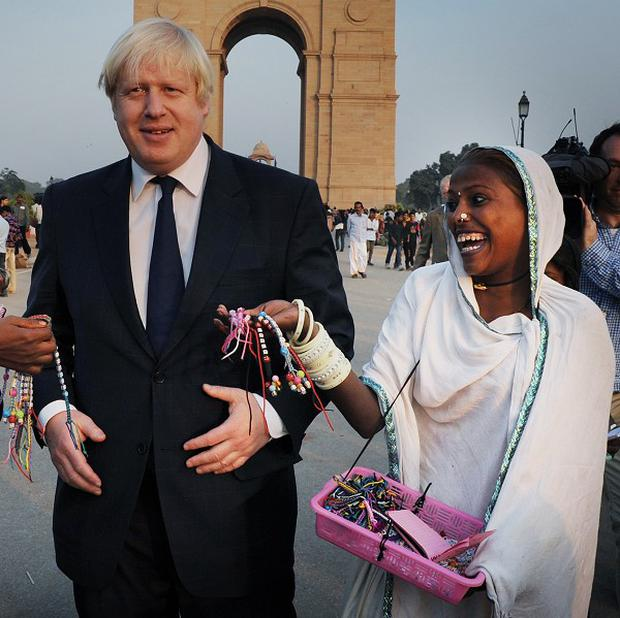 London Mayor Boris Johnson is chased by street vendors at India Gate in New Delhi