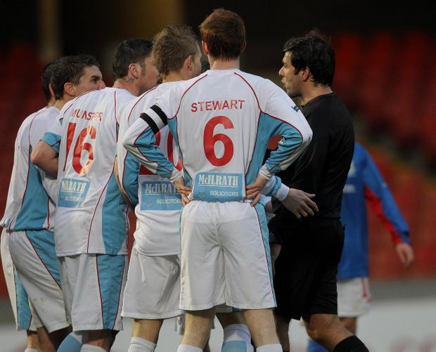 Andrew Davey is surrounded by Ballymena players after his controversial decision to award Linfield a penalty in Saturday's game