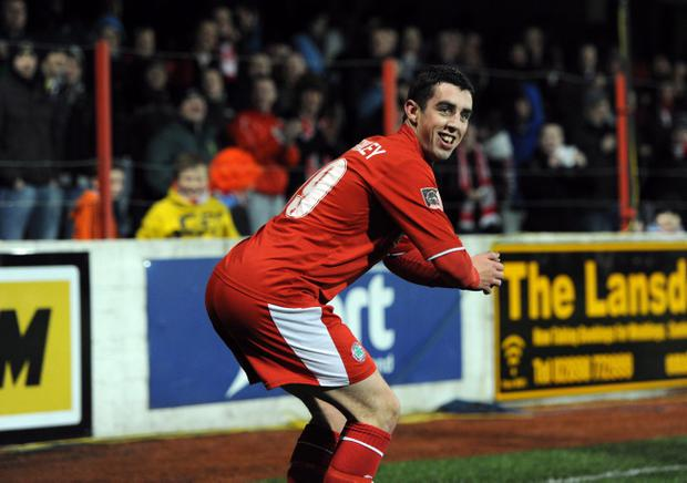 Joe Gormley performs a celebration wiggle in front of the Cliftonville fans after he opened the scoring against Lisburn Distillery