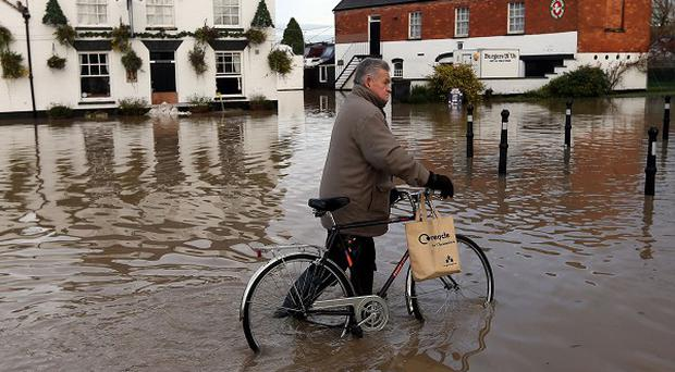 A pedestrian pushes his bike through flood water in Tewkesbury, Gloucestershire