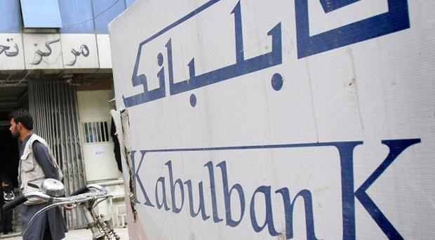 An Afghan man walks past by a branch of Kabul Bank in Kabul, Afghanistan (AP)