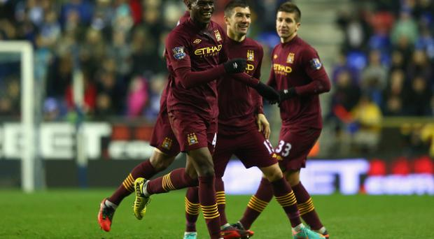 WIGAN, ENGLAND - NOVEMBER 28: Mario Balotelli (L) of Manchester City celebrates after scoring his sides opening goal during the Barclays Premier League match between Wigan Athletic and Manchester City at the DW Stadium on November 28, 2012 in Wigan, England. (Photo by Michael Steele/Getty Images)