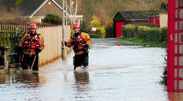Firefighters make their way along a flooded street in Old Malton, North Yorkshire