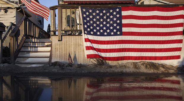 American flags are displayed on flood-damaged homes in the Breezy Point section of Queens (AP)