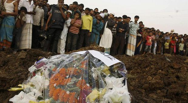 Hundreds of Bangladeshi mourners watch as the bodies of some of the victims of Saturday's fire in a garment factory are buried in Dhaka (AP)