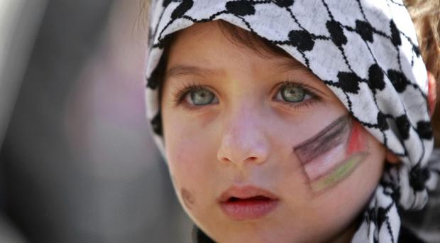 A girl with the Palestinian flag painted on her face attends a rally supporting the Palestinian UN bid for observer state status, in the West bank city of Ramallah, Thursday, Nov. 29, 2012.