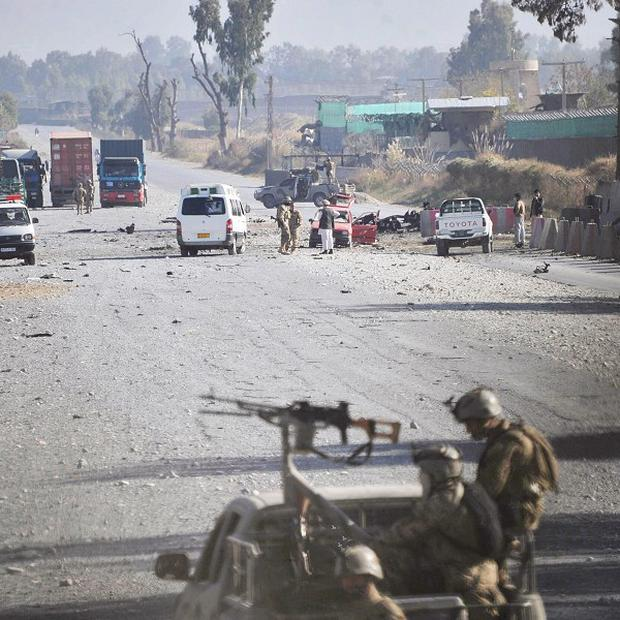 Afghan security forces block the road where Taliban suicide bombers attacked an air base in Jalalabad, east of Kabul (AP)