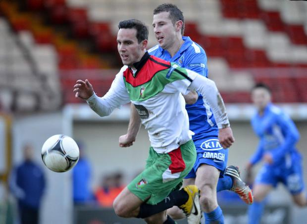 Glentoran's Andy Waterworth holds off the challenge of Leon Carters of Ballinamallard