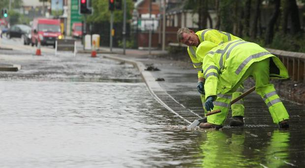 Council workers try to clear blocked drains during floods in the Twinbrook estate in Lisburn in July