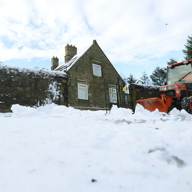 A snow plough clears paths in Tow Law, County Durham, after overnight snowfall