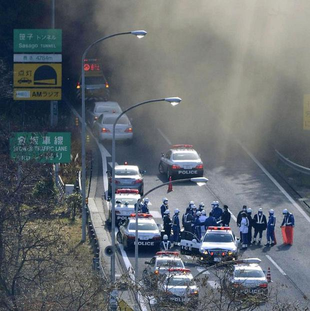 Police vehicles parked at the entrance as smoke billows out of the Sasago Tunnel on the Chuo Expressway in Koshu (AP/Kyodo News)