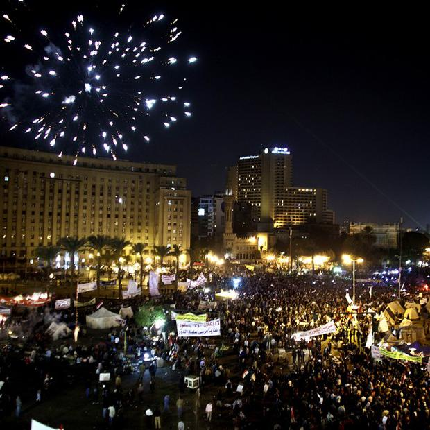 Fireworks burst over Tahrir Square as protesters gather in Cairo, Egypt (AP)