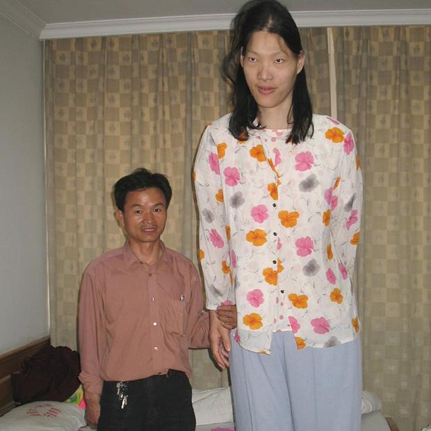 Yao Defen, the world's tallest woman, pictured here with her brother, has died aged 39 (AP)