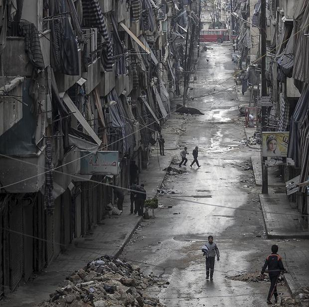 People walk past damaged homes during heavy fighting between Free Syrian Army fighters and government forces in Aleppo (AP)