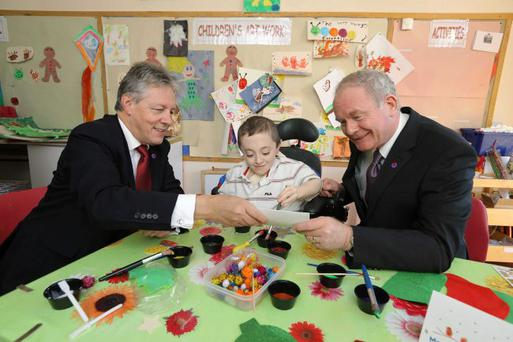 Working together: Peter Robinson and Martin McGuinness with Ryan Shannon making Christmas tree decorations on a visit to the NI Children's Hospice
