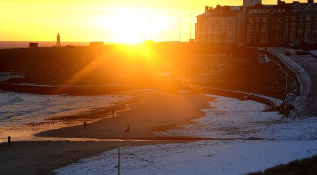 The sun rises over Tynemouth beach after a covering of snow.