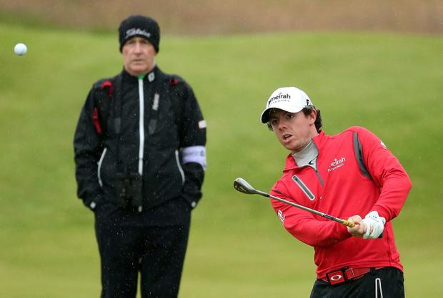 Coach Michael Bannon watches Rory McIlroy in action