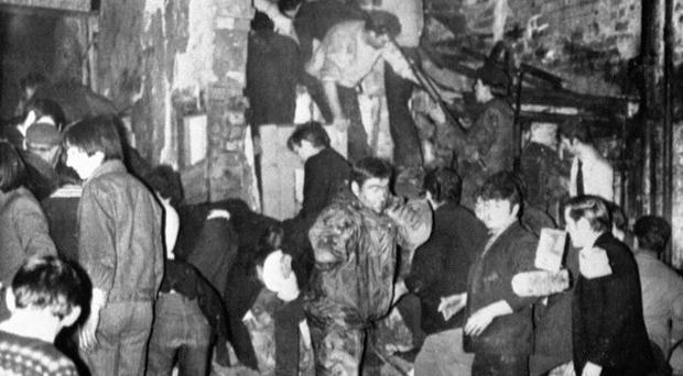 Rescuers, soldiers and civilians dig with bare hands in the smoking rubble of McGurk's bar, where 15 people died in a bomb blast in December 1971