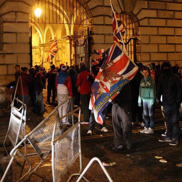 Loyalist protestors carrying Union flags break through the gate of the City Hall in Belfast