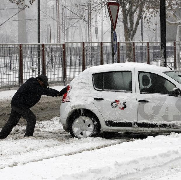 A man pushes a car on a snow-covered street in Belgrade, Serbia (AP)