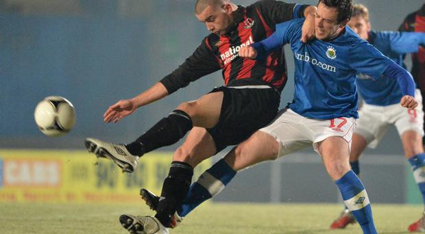 Crusaders captain Colin Coates and Gary Browne of Linfield battle for possession of the ball
