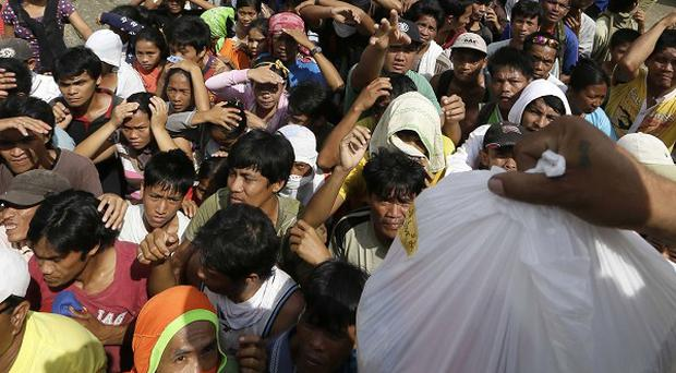 Residents affected by Typhoon Bopha queue up for relief goods being distributed in the Philippines (AP)