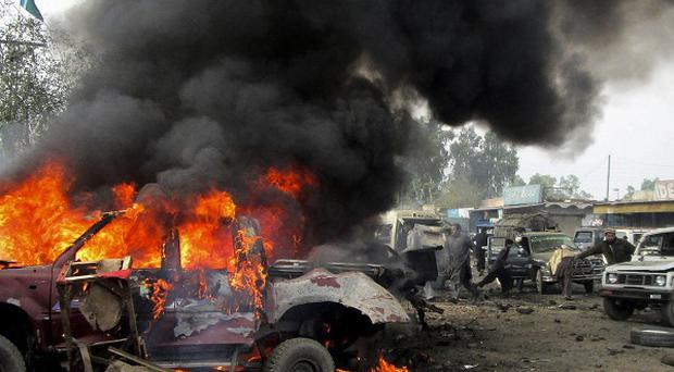 A Pakistani man walks past a burning vehicle after a blast in the Pakistani tribal area of Khyber (AP)