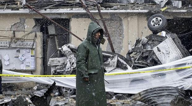 An Afghan security member stands at the scene of a car bomb explosion in Kabul (AP)
