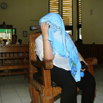 Briton Lindsay Sandiford covers her face as she sits on the defendant's chair facing drugs charges in court in Denpasar (AP)