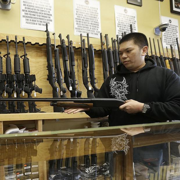 General manager Steve Alcairo holds a Winchester 1200 shotgun at High Bridge Arms Inc in San Francisco (AP/Jeff Chiu)