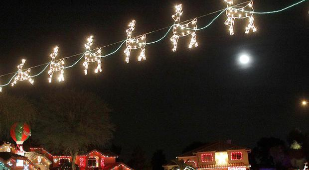 A US woman has sued her town after claiming she had been threatened with arrest if she did not take down her rude Christmas lights display