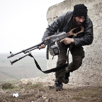 A Free Syrian Army fighter takes cover in Azaz (AP)