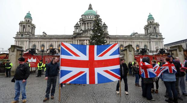 Loyalists and PSNI officers pictured at Belfast City Hall in December last year during a flag protest