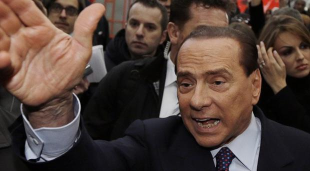 Former Italian premier Silvio Berlusconi arrives at Milan's central train station (AP)