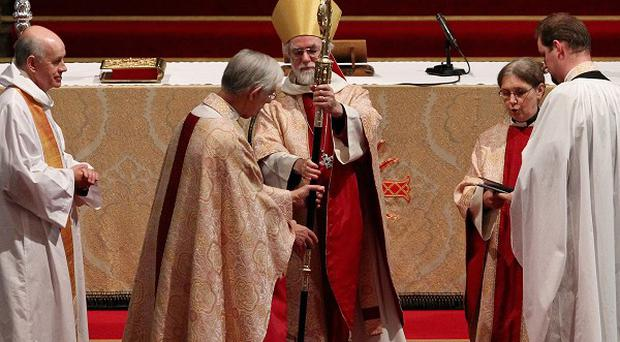 Dr Rowan Williams (centre) passes his crosier to the Dean of Canterbury Cathedral to mark the end of his role of as Archbishop of Canterbury