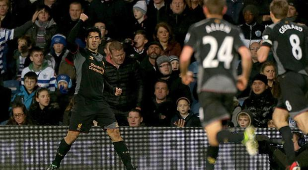 Liverpool's Luis Suarez celebrates scoring his side's second goal of the game during the Barclays Premier League match at Loftus Road, London