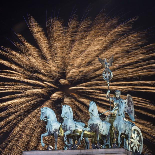 Fireworks explode in the sky above the Quadriga on the Brandenburg Gate during the New Year's celebrations in Berlin (AP/Markus Schreiber)
