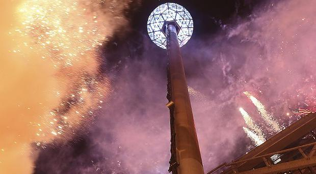 The fireworks explode as the Waterford crystal ball is raised at the beginning of Times Square new year celebrations in New York (AP)